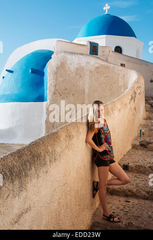 Young woman with colorful dress in front of typical Santorini church in the town of Oia, Greek Islands, Greece - Stock Photo