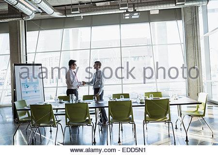 Businessmen handshaking in conference room - Stock Photo