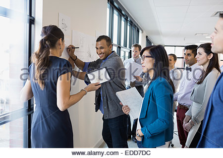 Business people working around plans on wall - Stock Photo