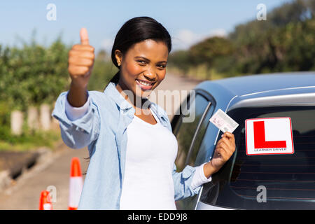 attractive African learner driver holding her driver's license - Stock Photo