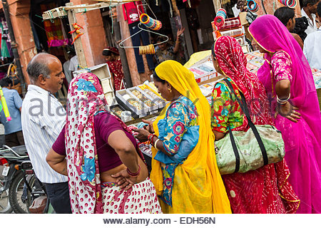 Women standing in street stall - India - Stock Photo