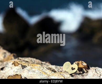 A bright beautiful metal heart is placed on top of a rock. In the background is a rocky beach and a breaking wave. - Stock Photo