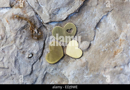 Three bright beautiful metal hearts are placed on a rock with natural salt on a beach. - Stock Photo