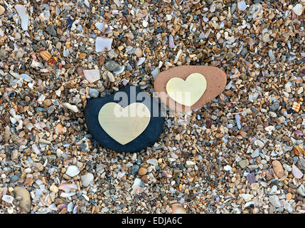 Two bright beautiful metal hearts are placed on two different rocks on sandy background. - Stock Photo