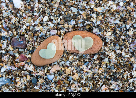Two bright beautiful metal hearts are placed on two red rocks on sandy background. - Stock Photo