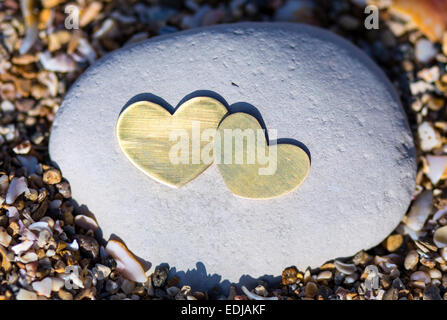 Two bright beautiful metal hearts are placed on a bright rock on sandy background. - Stock Photo