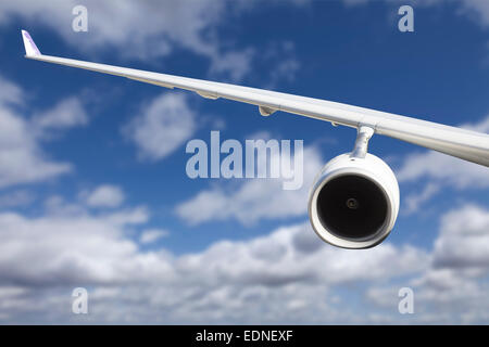 Large Airplane Wing Against Blue Sky and Clouds. - Stock Photo