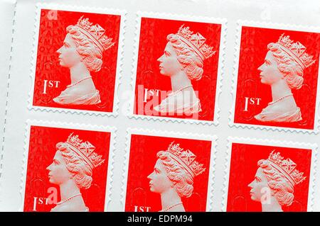 Red British first class royal mail postage stamps - Stock Photo