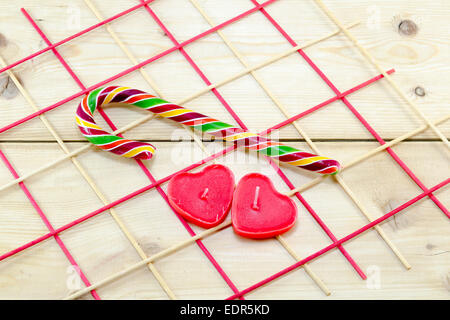 Colorful candy cane and heart shaped candles on a decorated wooden table - Stock Photo