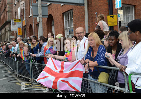 Onlookers hold a pink gay Union Flag at the Manchester Gay Pride Parade. - Stock Photo