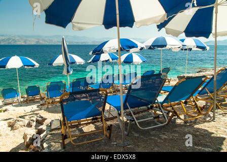 Sunbeds and umbrellas (parasols) on Kassiopi Beach, Corfu Island, Greece - Stock Photo
