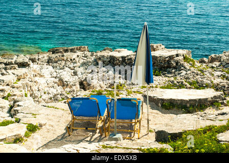 Sunbeds and umbrellas (parasols) on Kassiopi Beach, Corfu Island, Greece - Stock Photo