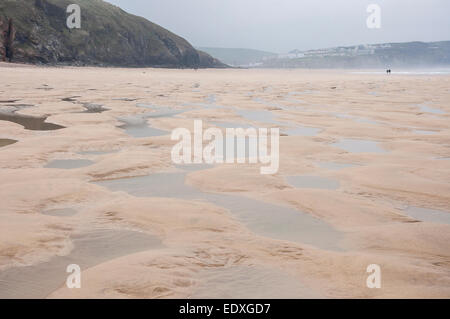 Wide expanse of sand and water at Perranporth beach in Cornwall. Looking back towards the cliffs and the village. - Stock Photo