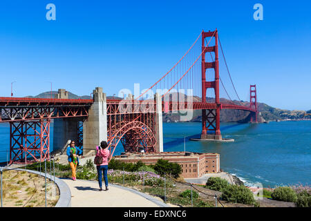 Tourists in front of the Golden Gate Bridge above Fort Point, Presidio park, San Francisco, California, USA - Stock Photo