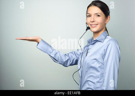 Smiling attractive friendly woman doing telemarketing or a promotion wearing a headset and extending her empty palm - Stock Photo