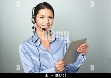 Portrait of Smiling Young Customer Representative Woman with Headset working with her Tablet Computer - Stock Photo