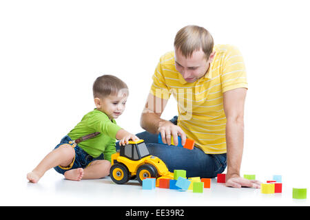 toddler boy and his father repair toy tractor - Stock Photo