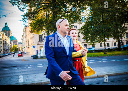 Senior couple walking along city street, Munich, Bavaria, Germany - Stock Photo