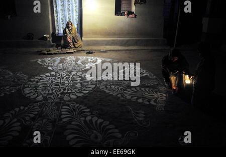 (150114) -- AGARTALA, Jan. 14, 2015 (Xinhua) -- A woman paints 'alpona' on the floor at Lankamura, 10 km away from - Stock Photo