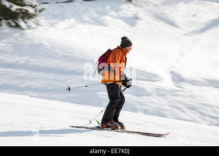 Skier with rucksack skiing down ski slope in winter sports resort in the Alps - Stock Photo