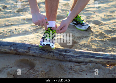 man at the beach that you fasten your shoes before a sport - Stock Photo