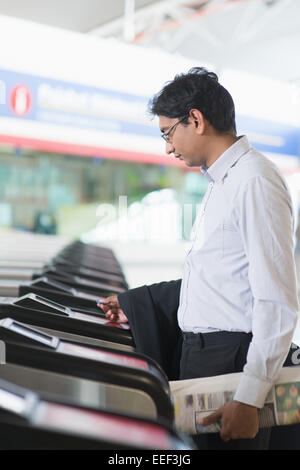 Asian Indian businessman at entrance of railway station, touching ticket token on gate barrier. - Stock Photo