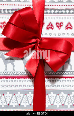 Close up of Christmas present with hand made red bow - Stock Photo