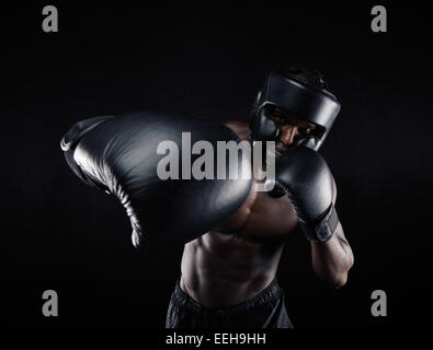 Portrait of African male practicing boxing against black background. Male boxer throwing a punch in front. Young - Stock Photo