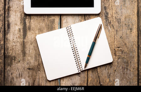 Workplace with digital tablet or pad and opened empty notebook with old golden fountain pen on wooden background - Stock Photo