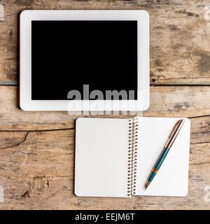 Digital pad with empty black screen and opened notebook with old fountain pen on wooden table - Stock Photo
