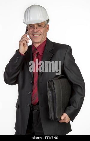 Architekt mit Aktentasche und Handy, telefoniert, Architect with safety-helmet and briefcase under her arm telephoning - Stock Photo