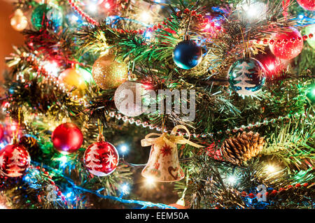 Part of Christmas tree- decorated with balls, bells and lights - Stock Photo
