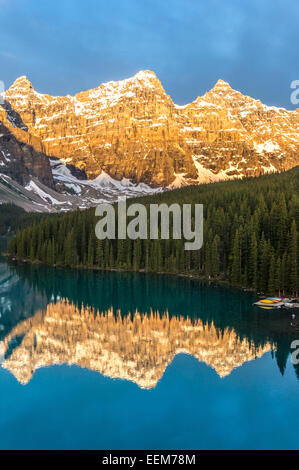 Canada, Banff National Park, Canadian Rockies, Mountains reflecting in calm lake at sunrise - Stock Photo