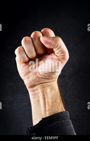 Riot protest fist raised in the air. Male clenched fist on dark grunge background. - Stock Photo