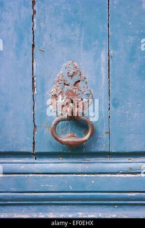 Old metal door knocker on blue painted wooden door - Stock Photo