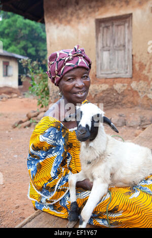 A villager poses with her sheep in Port Loko, Sierra Leone, West Africa. - Stock Photo