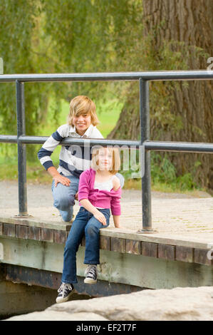 Siblings sitting on bridge - Stock Photo