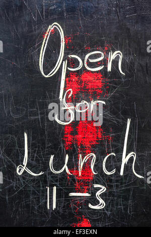 A will used blackboard sign with the words 'Open for Lunch' - Stock Photo