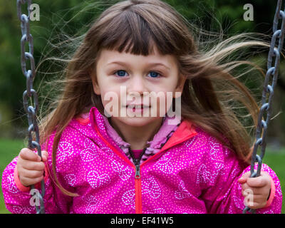 Young girl on a swing with hair blowing in the breeze. - Stock Photo