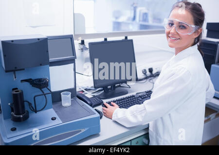 Portrait of a smiling young scientist with safety glasses - Stock Photo