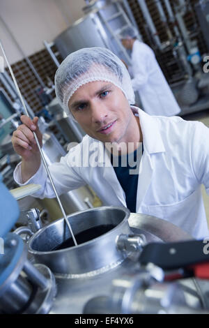 Smiling scientist using brewer in the container - Stock Photo