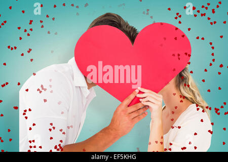 Composite image of attractive young couple kissing behind large heart - Stock Photo