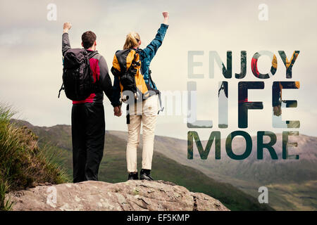 Composite image of excited couple reaching the top of their hike and cheering - Stock Photo