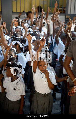 Students raising their hands, morning assembly, schoolyard, Basile Moreau primary school, Carrefour, Port-au-Prince - Stock Photo