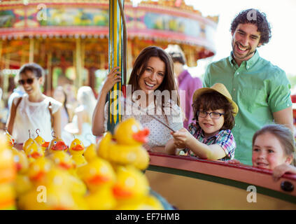 Parents with two children having fun with fishing game in amusement park - Stock Photo