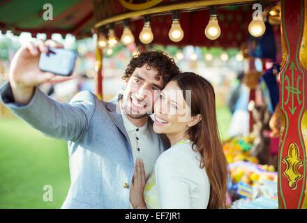 Smiling couple taking selfie in amusement park - Stock Photo