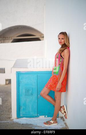 Woman leaning against wall - Stock Photo