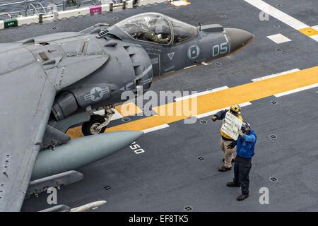 A US Sailor directs a US Marine Corps AV-8B Harrier II fighter aircraft to prepare for take off from the flight - Stock Photo