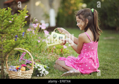 Girl (6-7) in pink dress gardening - Stock Photo