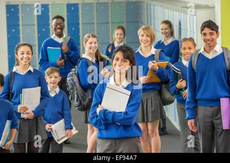 Group portrait of schoolchildren wearing school uniforms standing in corridor and smiling - Stock Photo
